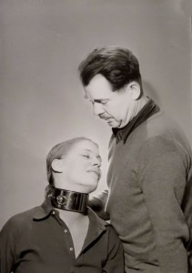 Woman in metal collar, man standing over her