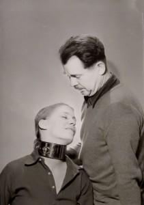 Woman in metal collar, man standing over her