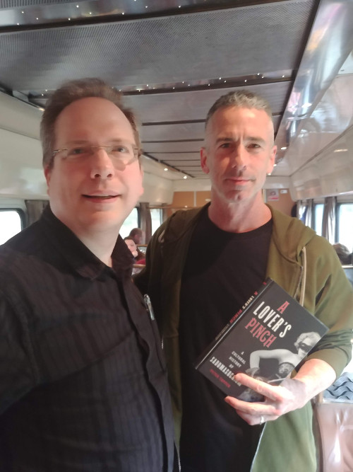 "Peter Tupper standing next to Dan Savage, holding a copy of ""A Lover's Pinch"""